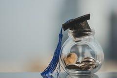 Sombrero de la graduaci?n en el dinero de las monedas en la botella de cristal en el fondo blanco imagenes de archivo