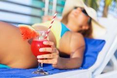 Sombrero de la mujer que sostiene el cóctel fresco de la bebida del smoothie del jugo de la sandía Imagen de archivo libre de regalías
