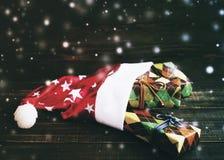 Sombrero de la Navidad de Papá Noel y cajas festivas en papel colorido Imágenes de archivo libres de regalías