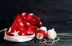 Sombrero de la Navidad de Papá Noel y de las esferas festivas del vidrio del abeto Imagenes de archivo
