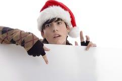 Sombrero de la Navidad del muchacho que desgasta joven que indica el cartel Foto de archivo libre de regalías