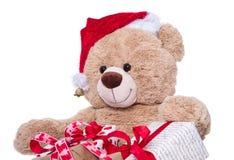 Sombrero de la Navidad del oso de peluche que lleva con los regalos aislados en los vagos blancos Foto de archivo