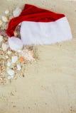Sombrero de la Navidad en la playa Papá Noel la arena cerca de cáscaras holiday Vacaciones del Año Nuevo Copie el espacio Capítul Fotografía de archivo