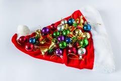 Sombrero de la Navidad, presentes y bolas hermosos de la Navidad en un casquillo rojo Imágenes de archivo libres de regalías