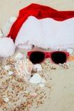 Sombrero de la Navidad y gafas de sol rojas en la playa Lentes de Papá Noel la arena cerca de cáscaras holiday Vacaciones del Año Fotos de archivo libres de regalías