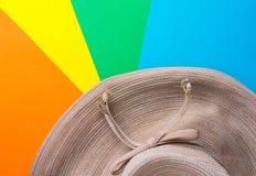 Sombrero de la paja de las mujeres brimmed amplias en fondo rayado del resplandor solar del molinillo de viento multicolor del ar imagen de archivo