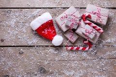 Sombrero de los regalos de Navidad, de Papá Noel y bastones de caramelo decorativos en envejecido imágenes de archivo libres de regalías