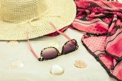 Sombrero de paja, abrigo de la ropa de playa del encubrimiento y vidrios de sol en una playa tropical imagenes de archivo