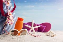 Sombrero de paja, bolso, vidrios de sol y chancletas en una playa tropical Imagen de archivo libre de regalías