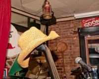 Sombrero de paja colgado en el extremo de una guitarra baja vertical imagen de archivo libre de regalías