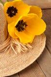 Sombrero de paja con el tulipán amarillo tres en la madera rústica Imagen de archivo