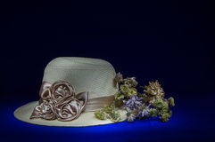 Sombrero de paja con las flores en vida negra del fondo-aún Foto de archivo libre de regalías