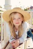 Sombrero de paja de la muchacha que desgasta en jardín imagen de archivo