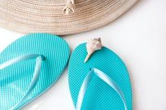Sombrero de paja del ` s de las mujeres elegantes, chancletas azules, cáscara del mar en el fondo concreto blanco, vacaciones de  Fotografía de archivo