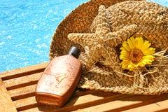 Sombrero de paja del verano con la loción que broncea Imagen de archivo