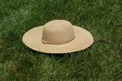 Sombrero de paja en hierba fotos de archivo