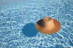 Sombrero de paja en la piscina Foto de archivo libre de regalías