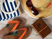 Sombrero de paja, gafas de sol, sketchbook del bolso de la playa y deslizadores Fotos de archivo libres de regalías