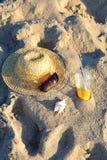 Sombrero de paja, gafas de sol, zumo de naranja y concha marina en la arena en la playa Fotos de archivo