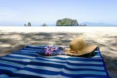 Sombrero de paja, gafas de sol y chancletas en una playa tropical fotos de archivo libres de regalías