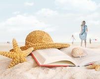 Sombrero de paja, libro y seashells en la arena Foto de archivo