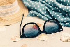 Sombrero de paja, vidrios de sol y abrigo de la ropa de playa del encubrimiento en una playa tropical imágenes de archivo libres de regalías