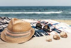 Sombrero de paja, vidrios de sol y abrigo de la ropa de playa del encubrimiento en una playa tropical imagen de archivo libre de regalías