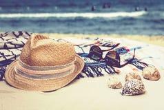 Sombrero de paja, vidrios de sol y abrigo de la ropa de playa del encubrimiento en una playa tropical con las c?scaras del mar imágenes de archivo libres de regalías
