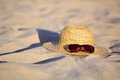 Sombrero de paja y gafas de sol en la arena en la playa Imagen de archivo libre de regalías