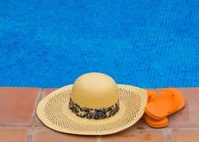 Sombrero de paja y sandalias por el lado de la piscina Foto de archivo