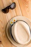 Sombrero de paja y vidrios de sol en el piso de madera Imágenes de archivo libres de regalías