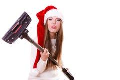 Sombrero de Papá Noel de la muchacha con el aspirador Fotografía de archivo