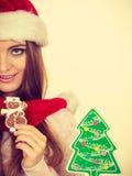 Sombrero de Papá Noel de la mujer con las galletas del pan de jengibre Navidad Imagenes de archivo