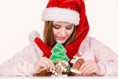 Sombrero de Papá Noel de la mujer con las galletas del pan de jengibre Navidad Imagen de archivo libre de regalías