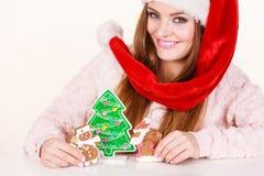Sombrero de Papá Noel de la mujer con las galletas del pan de jengibre Navidad Imagen de archivo