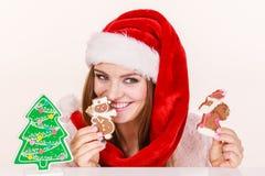 Sombrero de Papá Noel de la mujer con las galletas del pan de jengibre Navidad Fotografía de archivo libre de regalías