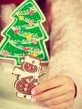 Sombrero de Papá Noel de la mujer con las galletas del pan de jengibre Navidad Foto de archivo libre de regalías