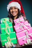 Sombrero de Papá Noel de la raza mixta de la muchacha con las cajas de regalo Foto de archivo libre de regalías