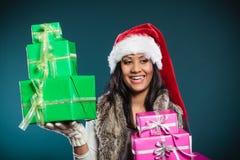 Sombrero de Papá Noel de la raza mixta de la muchacha con las cajas de regalo Imagenes de archivo