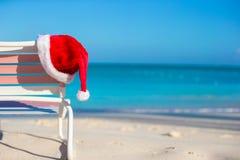 Sombrero de Papá Noel del primer en longue de la silla en tropical Foto de archivo libre de regalías