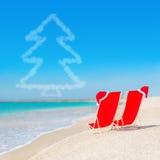 Sombrero de Papá Noel en los sillones en la playa blanca de la arena contra el mar Imagen de archivo