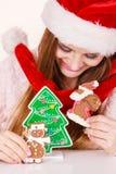 Sombrero de Papá Noel de la mujer con las galletas del pan de jengibre Navidad Fotos de archivo