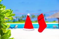Sombrero de Papá Noel y media rojos de la Navidad entre la palma Fotografía de archivo libre de regalías