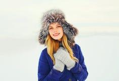 Sombrero de piel sonriente feliz de la mujer del retrato de la moda del invierno que lleva sobre nieve Imagen de archivo
