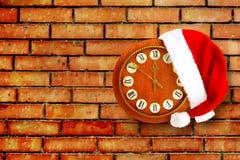 Sombrero de Santa Claus el la noche del Año Nuevo en el reloj viejo Imagenes de archivo
