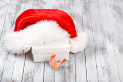Sombrero de Santa Claus sobre la caja de regalo en fondo de madera Concepto de las vacaciones de invierno Año Nuevo del gallo Fotografía de archivo libre de regalías