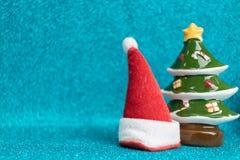 Sombrero de Santa Claus y árbol de pino rojos en fondo chispeante Imagenes de archivo