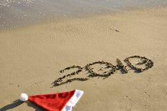 Sombrero de Santa con Año Nuevo en la arena. Fotografía de archivo