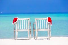 Sombrero de santa del primer en silla en la playa blanca tropical Fotos de archivo