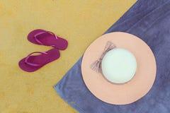 Sombrero de Sun con chancletas en la playa Imagen de archivo libre de regalías